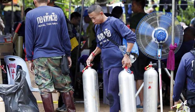 Personal de la Marina tailandesa carga tanques de oxígeno durante las operaciones de rescate del equipo de fútbol infantil y su asistente de entrenador en la cueva Tham Luang, en Tailandia.