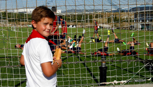 Un joven aficionado rojillo presencia uno de los primeros entrenamientos de Osasuna la pasada temporada, el que tuvo lugar el 11 de julio en plenas fiestas de San Fermín.