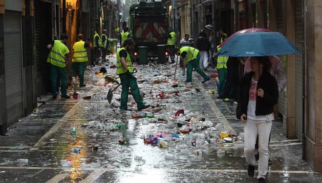 foto de Los servicios de limpieza recogen la basura y los vasos de plástico tras una noche de fiesta.