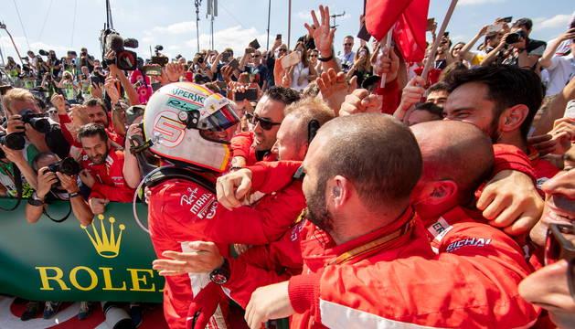 Vettel, felicitado por los mecánicos de Ferrari.