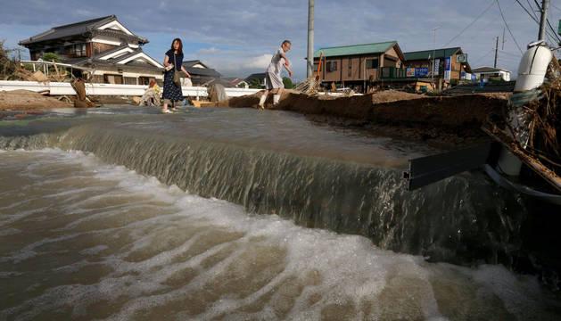 foto de Varios japoneses intentan sortear una avalancha de agua provocada por las lluvias torrenciales.