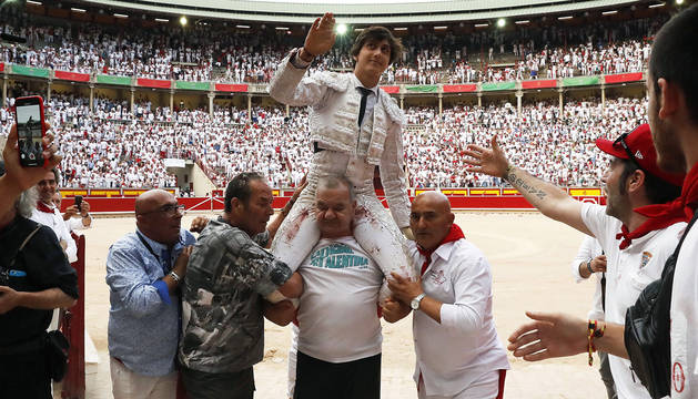 El torero Andrés Roca Rey sale a hombros de la Plaza de Toros de Pamplona tras cortar tres orejas en la séptima corrida de la Feria del Toro de San Fermín.