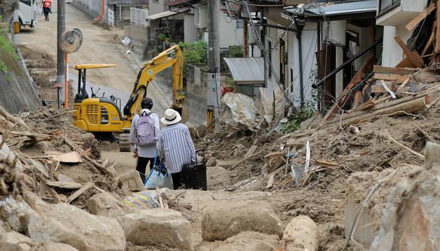 Dos ancianos cargan con sus pertenencias por una zona arrasada por las inundaciones de camino a un centro de alojamiento temporal en Hiroshima (Japón).