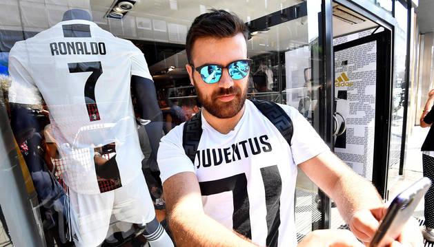 Un aficionado del Juventus posa con la nueva camiseta que lucirá Cristiano Ronaldo frente a la tienda oficial del Juventus en Milán.