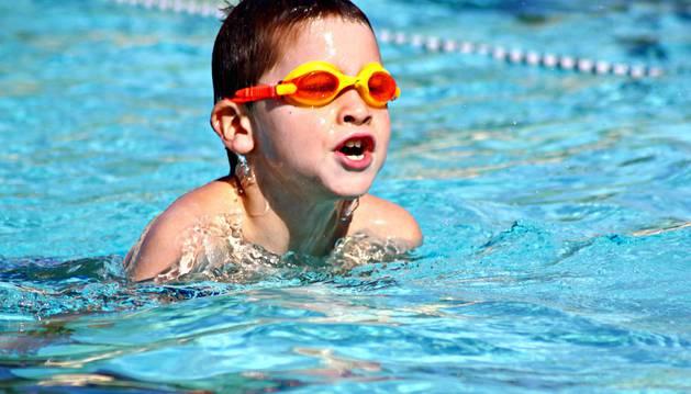 Un niño nada en una piscina en una foto de archivo.