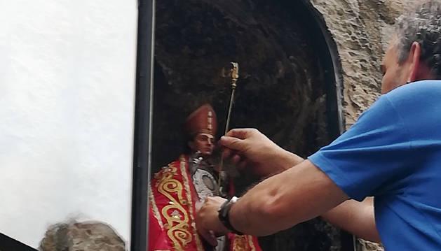 Un operario municipal coloca la imagen habitual de San Fermín en la hornacina de Santo Domingo.