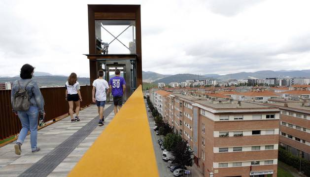 Varias personas se dirigen por la pasarela para utilizar el décimo elevador de Pamplona.