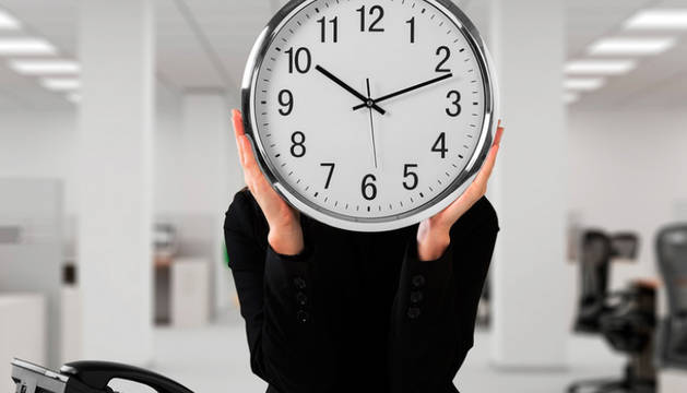 Una persona, tras un reloj en una oficina.