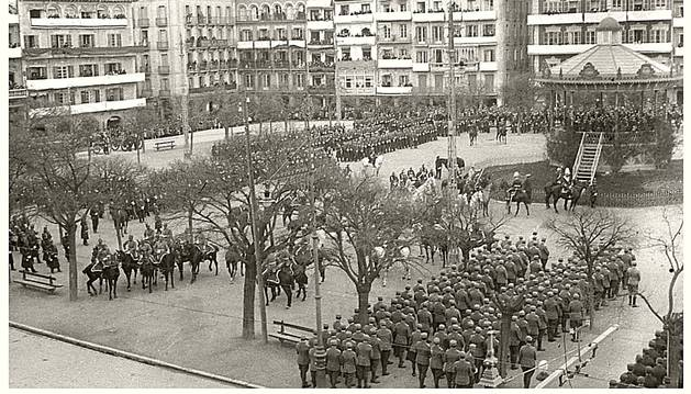 23 DE MARZO DE 1924. Vista de la mitad de la plaza del Castillo, entonces oficialmente de la Constitución, con distintas unidades militares, formadas para asistir al acto de la jura de bandera de los nuevos reclutas. Se aprecia el antiguo kiosco para los conciertos de las bandas de música, que en 1943 fue sustituido por el actual.