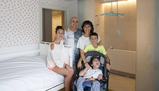 David Erice y Míriam Morteruel, con sus tres hijos: Adriana, Álvaro y Anne. La familia posa en la adaptación adaptada de Anne. Un sistema de rieles en el techo permite trasladarla con grúa de la cama a la camilla.