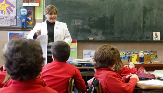 Una profesora atiende a sus alumnos en clase.