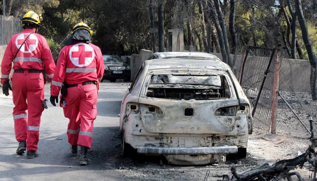 Miembros de la Cruz Roja caminan junto a un vehículo calcinado en una zona afectada por los incendios en Argyra Akti, en Mati (Grecia).