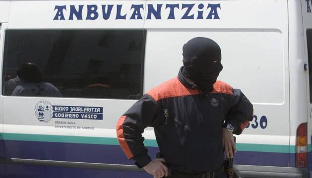 Un ertzaina, junto a una ambulancia, en una imagen de archivo.