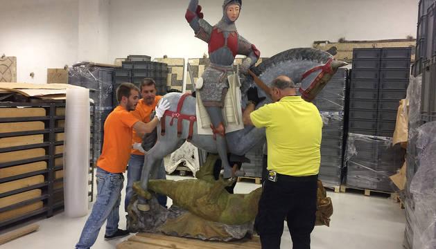 Un grupo de operarios traslada la talla policromada de San Jorge, de la iglesia de San Miguel de Estella, a los almacenes de Patrimonio Histórico de Arqueología de la Dirección General de Cultura.