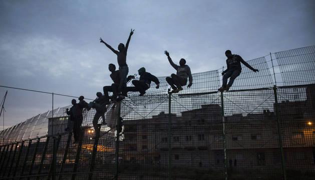 Un grupo de inmigrantes subsaharianos que piden amparo encaramados en la alambrada fronteriza de Melilla.