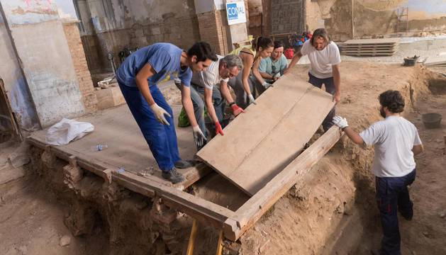 Alumnos del Taller de Arqueología de San Nicolás, junto a su profesor Juanjo Bienes -segundo por la dcha.- levanta la tapa de un enterramiento.