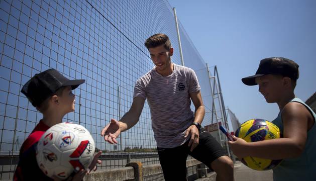 Dos jóvenes aficionados rojillos se acercan a David García en Tajonar para que les firme el balón.