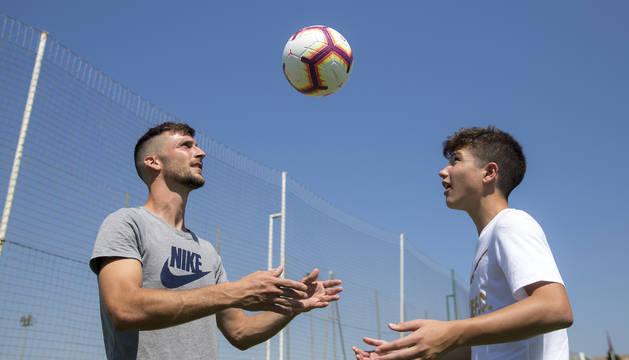 Oier Sanjurjo y Lucas Ibáñez se pasan de cabeza el balón.
