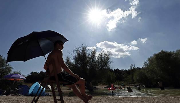 Varias personas se alivian del calor en el pantano de Alloz y en el río Arga a su paso por Irotz.
