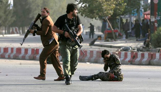 Miembros de las fuerzas de seguridad afganas protegen a un hombre herido en Kabul.