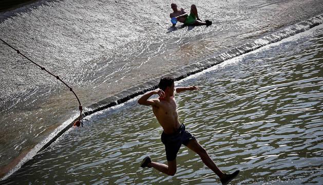 Dos jóvenes se refrescan en el río Arga a su paso por Pamplona.