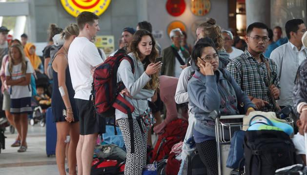 Turistas extranjeros esperan este lunes en los mostradores de facturación del aeropuerto Internacional Praya en Lombok (Indonesia).