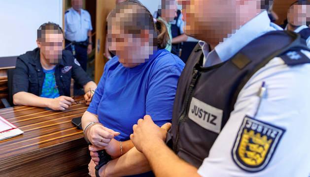 Los acusados Christian L. (izquierda) y Berrin T. (centro) entran en la sala del tribunal durante su juicio por abusos sexuales de su hijo en el Tribunal Regional de Friburgo.