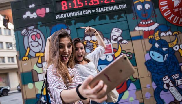 Dos jóvenes se fotografían con el reloj de Kukuxumusu que anunciaba la cuenta atrás para San Fermín.