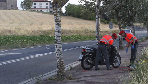 Dos policías forales atienden un accidente de moto.