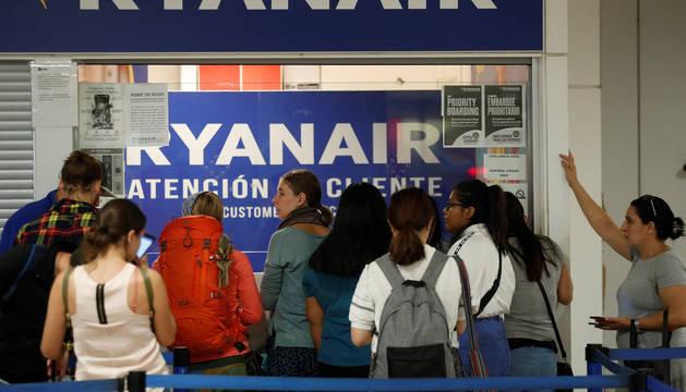 Varios pasajeros esperan ante el mostrador de atención al cliente en el Aeropuerto Adolfo Suárez - Madrid Barajas
