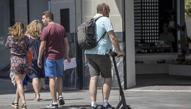 Un usuario del patinete eléctrico circula por una zona peatonal