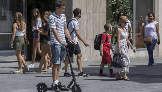 Un conductor de patinete eléctrico se desplaza por la avenida Carlos III.
