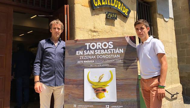 Los dos Hermoso de Mendoza, padre e hijo, posan ante la sociedad Gaztelubide con el cartel que anuncia la Feria de San Sebastián.
