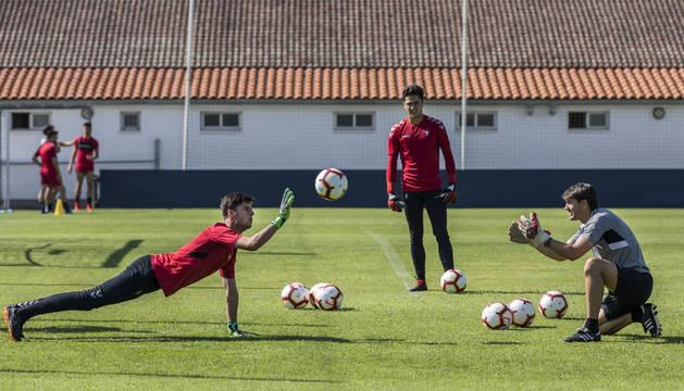 Juan Pérez, en el suelo, e Iván Martínez realizan ejercicios de calentamiento con Richard Sanzol en un entrenamiento reciente en Tajonar.