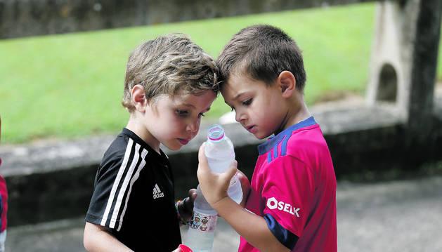 Dos jóvenes aficionados de Osasuna hidratándose en un día de pretemporada en Tajonar.