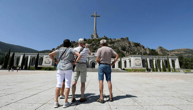 Varios visitantes fotografían el monumento del Valle de los Caídos.