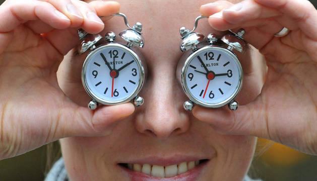Una persona con dos relojes, uno a las tres y otro a las dos.