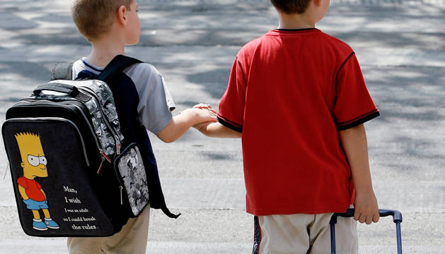 Dos niños, uno con mochila a la espalda, y otro con carrito.