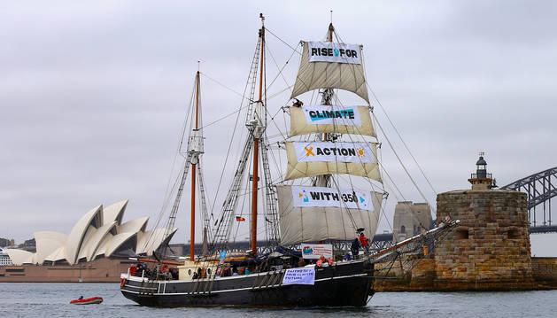 Un barco exhibe varias pancartas mientras navega en el puerto de Sydney en Australia como parte de las protestas mundiales por el cambio climático.
