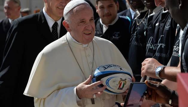 El papa Francisco (c) recibe una pelota de rugby firmada por los miembros de un equipo formado por refugiados tras su audiencia general en la Plaza de San Pedro del Vaticano, en el Vaticano
