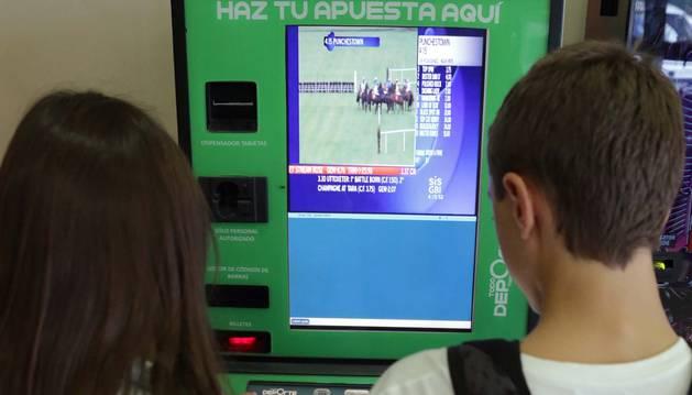 Dos menores, frente a una máquina de apuestas deportivas.