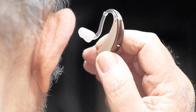 Un hombre se coloca un audífono.