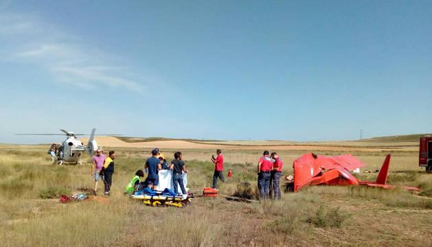 Servicios de emergencia, junto al herido y, a la derecha, la avioneta accidentada.