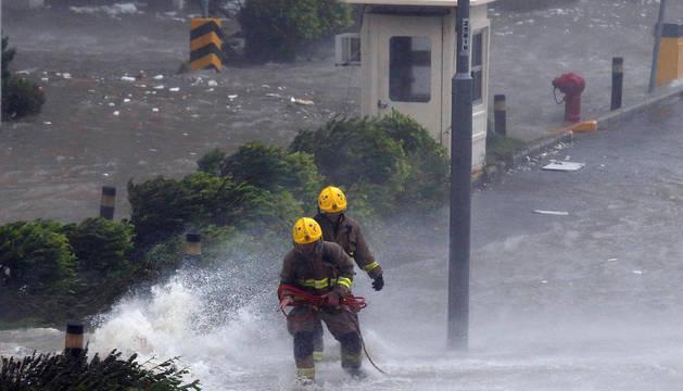 Bomberos luchan contra las olas en Heng Fa Chuen, un área residencial cerca de la costa en Hong Kong.