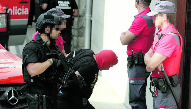 Agentes de la Policía Foral introducen a Juan Carlos Jiménez, con el rostro tapado, en los juzgados de Aoiz.
