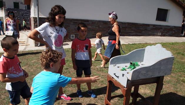 Pequeños se divierten tratando de acertar con sus lanzamientos en el tradicional juego de la rana.