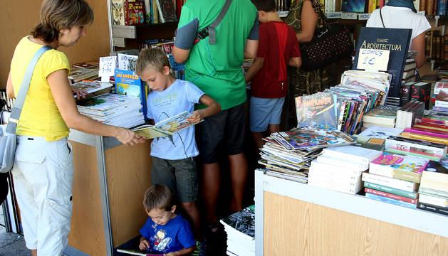 Familias y jóvenes ojeando varios cómics en uno de los stands de la Plaza del Castillo.
