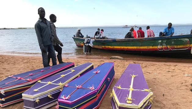 Voluntarios arreglan los ataúdes que contienen los cadáveres recuperados de los pasajeros del ferri que volcó en el lago Victoria.
