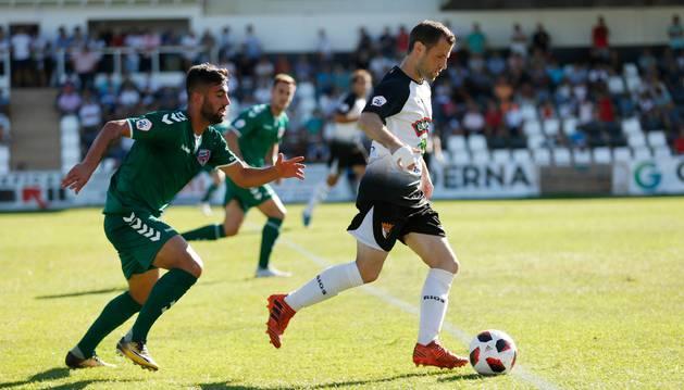 El extremo del Tudelano Ibai Ardanaz conduce el balón en el partido de ayer perseguido por un rival del Leioa.