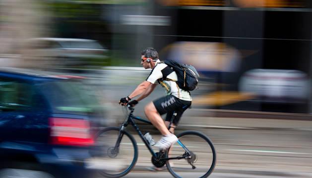 foto de Un ciclista circulando con auriculares por ciudad.